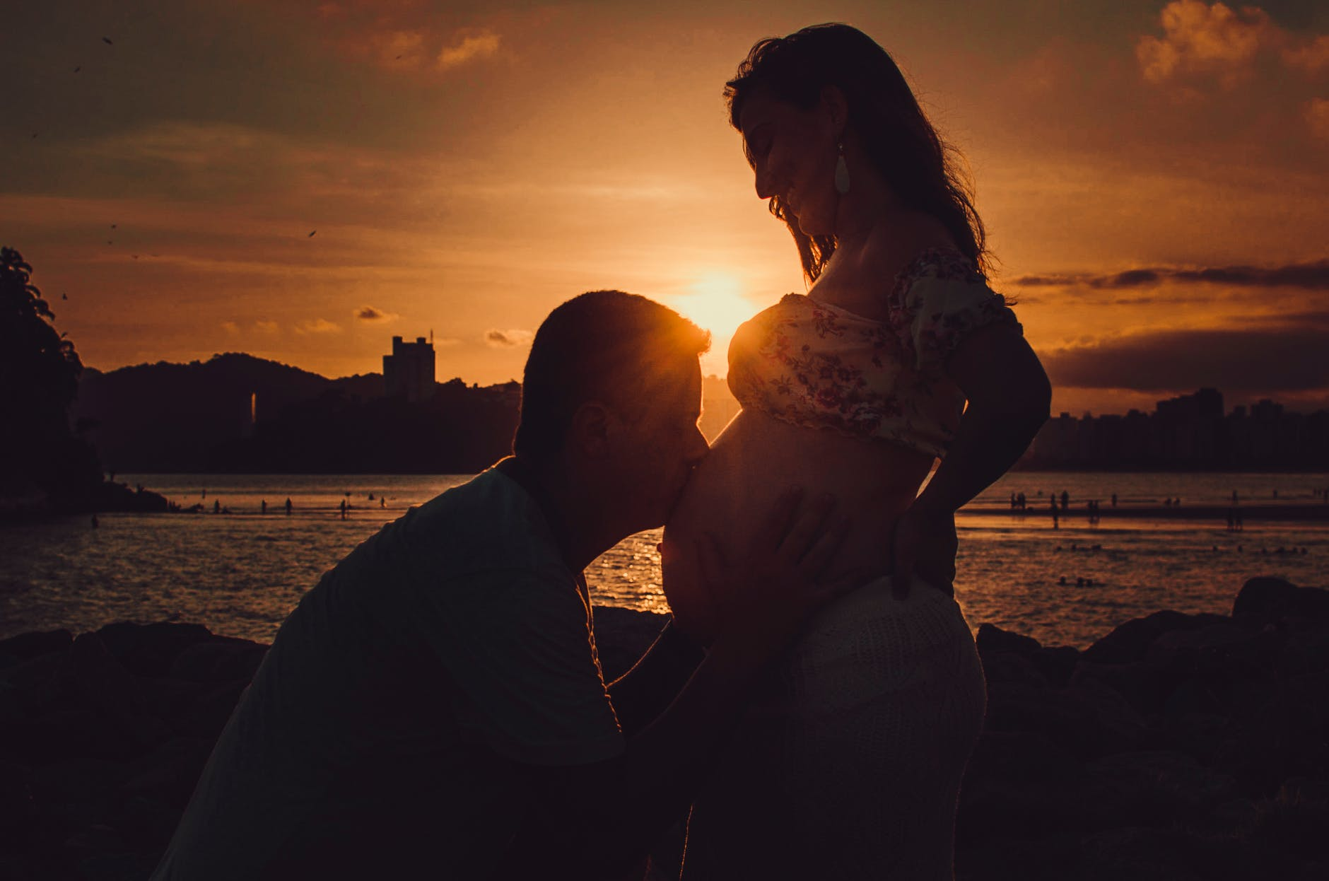 silhouette photography of man kissing belly of a pregnant woman