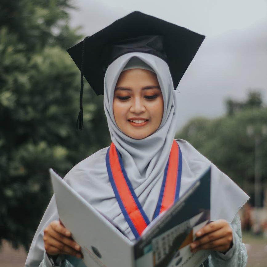 Ilustrasi wisuda woman in white academic dress holding book