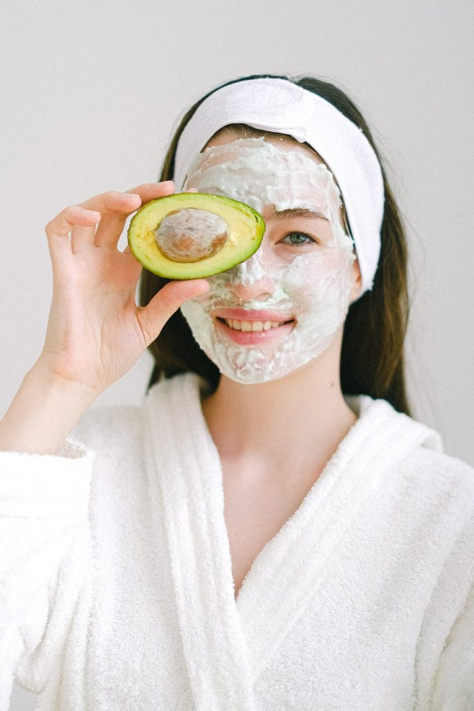 cheerful woman with mask and avocado