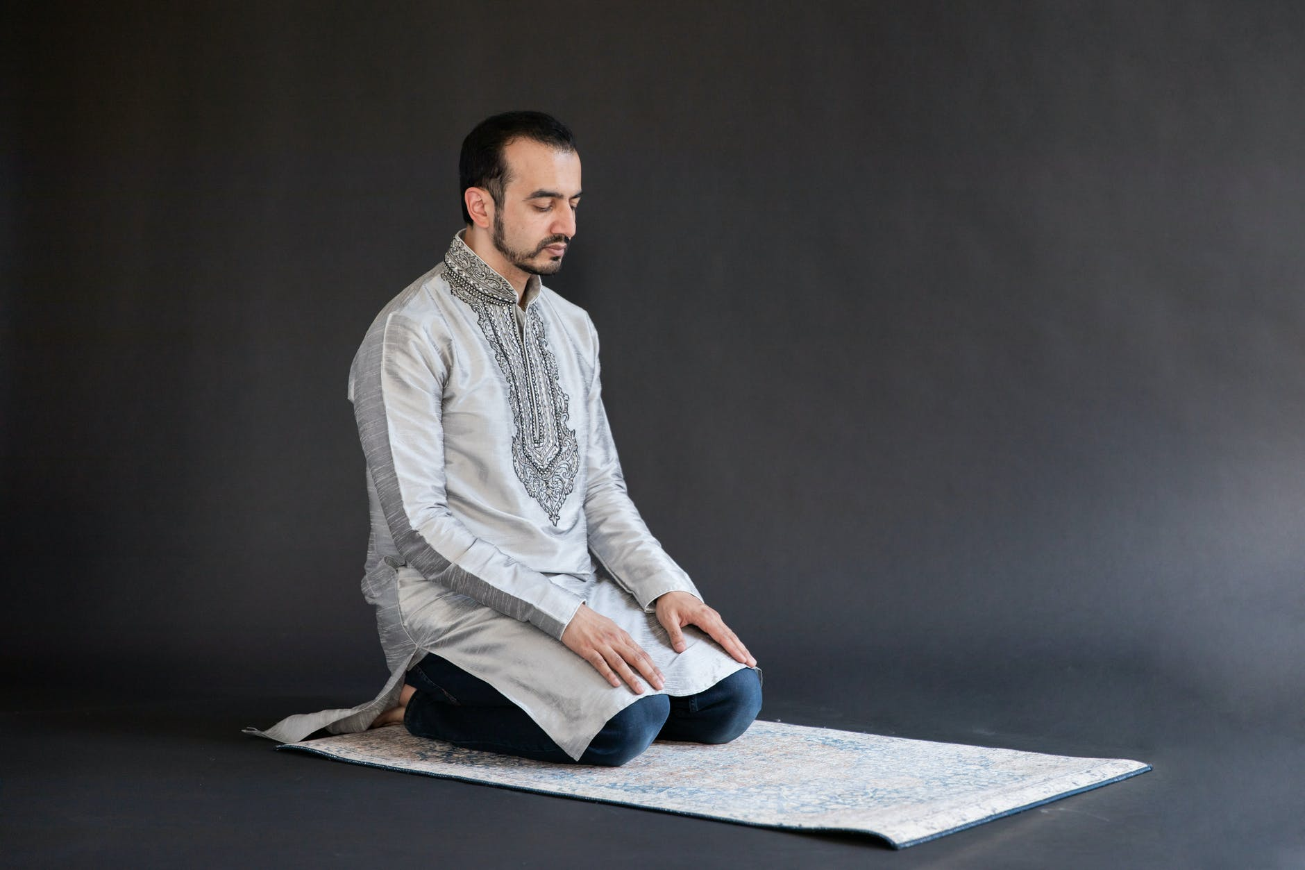 man kneeling on a carpet